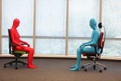 Paar die in volledige lichaams elastische kostuums op leunstoelen in zonnige ruimte zitten Stock Foto