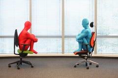 Paar die in volledige lichaams elastische kostuums op leunstoelen in zonnige ruimte zitten Royalty-vrije Stock Afbeeldingen