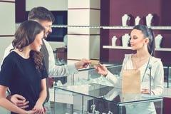 Paar die voor aankoop bij juwelenopslag door kaart betalen stock fotografie