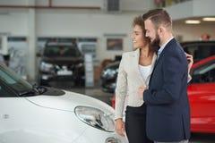 Paar die zich in autocentrum bevinden en auto samen kiezen royalty-vrije stock afbeeldingen