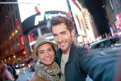 Paar die zich in de stad van New York bij nacht bevinden Stock Afbeelding