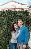 Paar die zich dichtbij huis met klimopomheining bevinden royalty-vrije stock fotografie