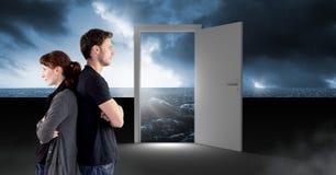 Paar die zich door open deur met surreal donkere overzeese gloed en hemel bevinden royalty-vrije stock afbeelding