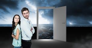 Paar die zich door open deur met surreal donkere overzeese gloed en hemel bevinden stock foto's