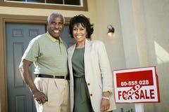 Paar die zich door Verkocht Real Estate-Teken bevinden stock afbeeldingen