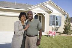 Paar die zich in Front Of House For Sale bevinden Royalty-vrije Stock Foto