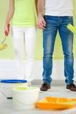 Paar die zich met het schilderen van hulpmiddelen bevinden Royalty-vrije Stock Afbeeldingen