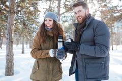 Paar die zich met thermosflessen in de winterpark bevinden Stock Fotografie