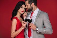 Paar die zich met die wijnglazen bevinden op rood worden geïsoleerd Royalty-vrije Stock Foto's