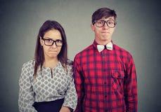 Paar die zich naast elkaar bevinden die hun lippen met ongenoegen drukken die slechte stemming hebben stock foto