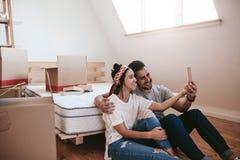 Paar die zich in nieuwe plaats bewegen en een selfie maken royalty-vrije stock foto