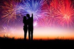 Paar die zich op de heuvel bevinden en op het vuurwerk letten Stock Afbeeldingen