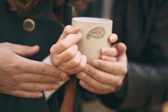 Paar die zijn handen op een kop van hete thee verwarmen Stock Fotografie