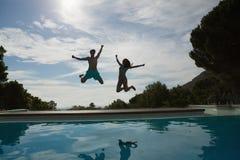 Paar die in zwembad springen Stock Afbeeldingen