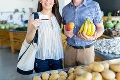 Paar Doen die in Voedselopslag winkelen met Creditcard royalty-vrije stock afbeeldingen