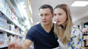 Paar duwend boodschappenwagentje in supermarkt stock videobeelden