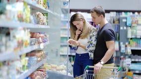Paar duwend boodschappenwagentje in supermarkt stock video