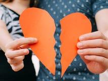 Paar een halve hartvorm houden die apart brekend - scheiding, spli royalty-vrije stock afbeeldingen