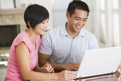 Paar in eetkamer met laptop het glimlachen Stock Foto's