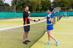 Paar eines Tennisspielerrüttelns überreicht das Netz Lizenzfreies Stockbild