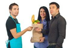 Paar en bediende bij kruidenierswinkel Royalty-vrije Stock Afbeeldingen
