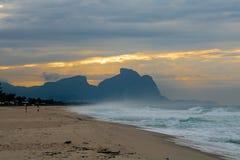 Paar en hond die op het strand van Barra da Tijuca in een mooie dageraad met de steen van Gavea op de achtergrond lopen - Rio de  stock fotografie