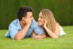 Paar in en liefde die elkaar die op het gras liggen dateren kijken stock fotografie