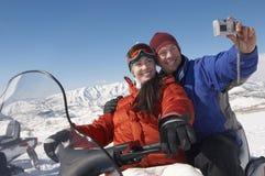Paar-fotografierende Selbst mit Digitalkamera auf Schneemobil fahrung Lizenzfreies Stockfoto