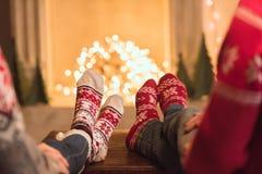 Paar in gebreide sokken dichtbij open haard stock foto