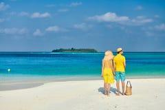 Paar in geel op tropisch strand in de Maldiven stock fotografie