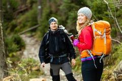 Paar gelukkige wandelaars die in bergen lopen royalty-vrije stock fotografie