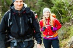 Paar gelukkige wandelaars die in bergen lopen stock foto's