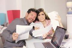 Paar gillen doen schrikken over belastingen en rekeningen Stock Fotografie