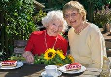 Paar glimlachende vrouwen die pastei in koffie eten stock afbeeldingen