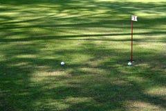 Paar golfballen dichtbij gatenvlag 5 Stock Afbeeldingen