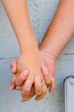 Paar hält Hände an Stockbild