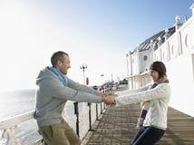 Paar-Händchenhalten und auf Pier herum spinnen lizenzfreies stockbild
