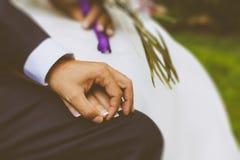 Paar-Hände an einem Hochzeitstag Stockfotografie