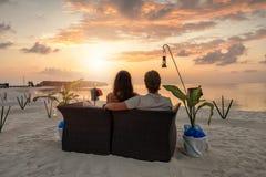 Paar hat eine romantische Sonnenuntergangabendesseneinrichtung Stockfotografie