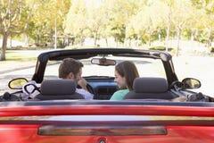 Paar in het convertibele auto glimlachen Stock Afbeelding