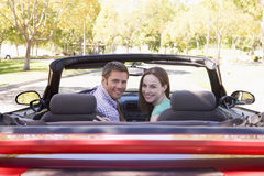 Paar in het convertibele auto glimlachen Stock Foto's