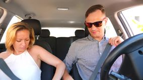 Paar het drijven in de auto, een man en een vrouw berijden samen in de auto door de straten van de stad en zien rond eruit stock video
