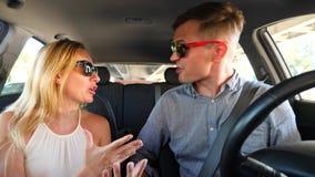 Paar het drijven in de auto, een man en een vrouw in de auto door de straten van de stad en de ruzie Schreeuw bij elkaar stock videobeelden