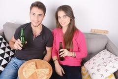 Paar het drinken bier en het eten van pizza Stock Afbeelding