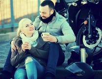 Paar het drinken koffie dichtbij motorfiets stock afbeelding