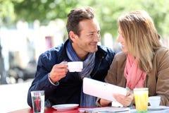 Paar het drinken koffie en in openlucht het gebruiken van tablet Royalty-vrije Stock Foto