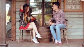 Paar het drinken thee/koffie in de Wilde Westennen, in Westelijk huis Meisje in hoed met lang haar Meisje en jongensglimlach, het stock video