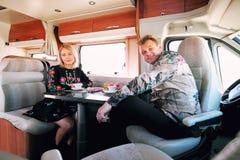 Paar het drinken theezitting in kampeerautobestelwagen stock afbeeldingen