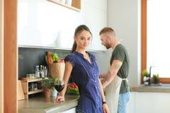 Paar het drinken wijn terwijl het koken in de keuken Stock Foto
