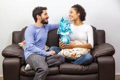 Paar het hangen uit in de woonkamer terwijl de vrouw een CH houdt stock afbeeldingen
